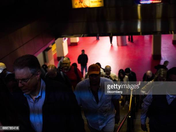 Commuters walk up the stairs from a Long Island Railroad Co train platform inside Pennsylvania Station in New York US on Friday May 26 2017...