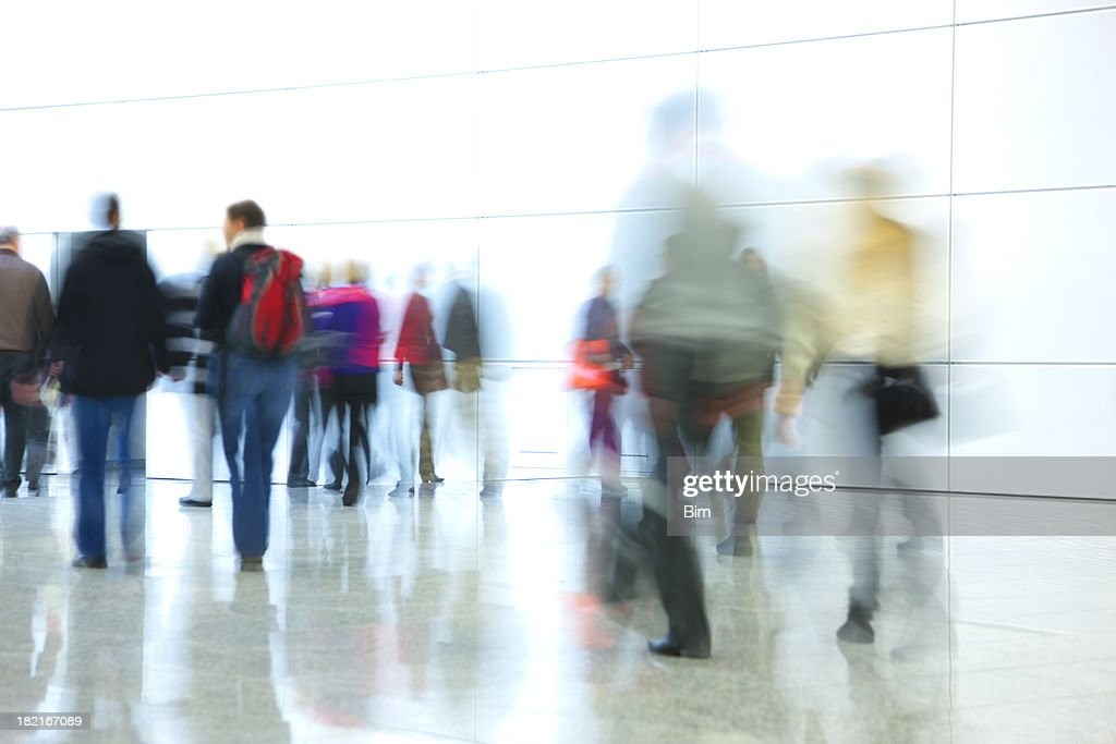 Blurred Silhouettes of Walking People in Hallway