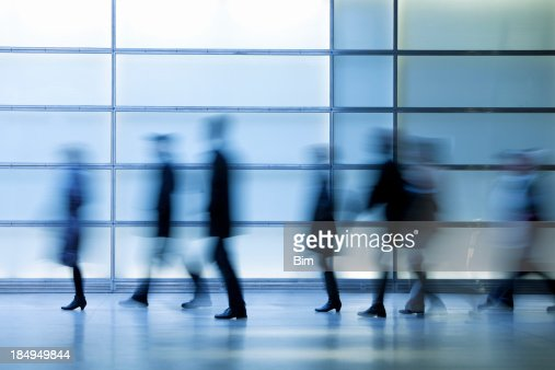 Commuters Walking in Modern Glass Interior, Blurred Motion