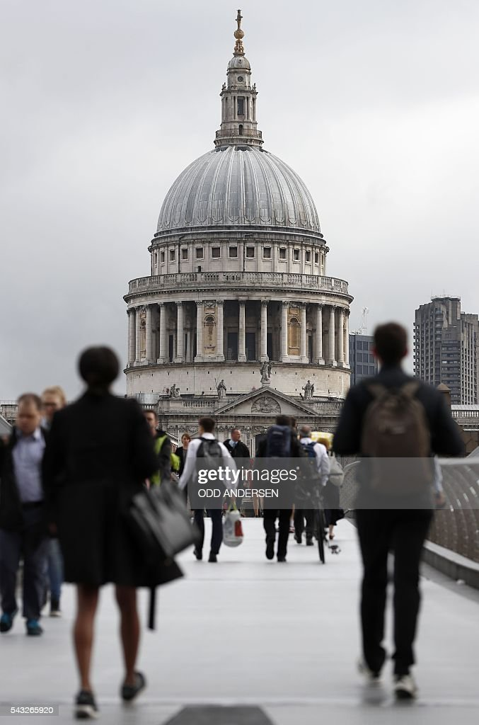 Commuters walks across the Millennium Bridge towards St Paul's Cathedral and the City Of London shelters on June 27, 2016. Britain should only trigger Article 50 to leave the EU when it has a 'clear view' of how its future in the bloc looks, finance minister George Osborne said Monday following last week's shock referendum. London stocks sank more than 0.8 percent in opening deals on Monday, despite attempts by finance minister George Osborne to calm jitters after last week's shock Brexit vote. / AFP / ODD
