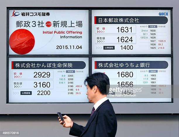 A commuters walks past an electric board displaying newly debuted Japan Post companies share price on November 4 2015 in Tokyo Japan The three...