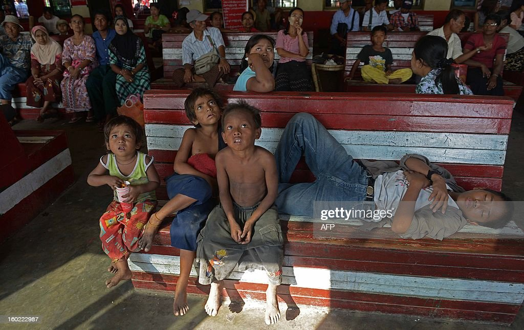 Commuters watch TV as they wait at a ferry pier in Yangon on January 28, 2013. Myanmar on January 28 announced a deal with international lenders to cancel nearly 6 billion USD of its debt, another milestone in the rapid transformation of the former junta-ruled nation. AFP PHOTO/Ye Aung THU