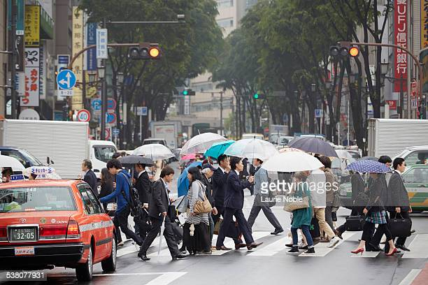 Commuters with umbrellas crossing road, Shibuya