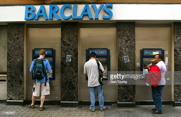 Commuters withdraw cash from ATM's outside a branch of Barclays Bank July 29 2002 on Regent Street in London England Barclays will announce its...