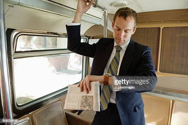 Commuting businessman looking at watch in bus