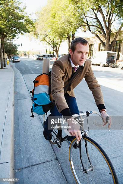 Commuting man riding bicycle on street