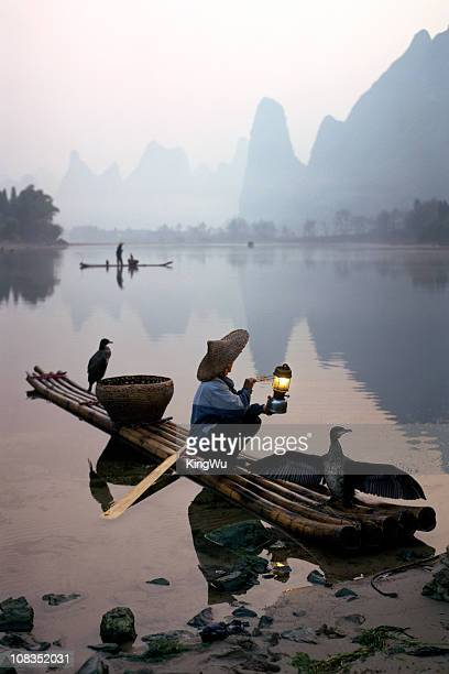 Comorant 鳥漁師のボートに座るの漓江