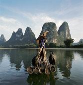 Comorant fisherman standing on bamboo raft