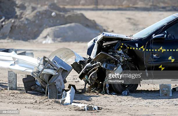 A compact coupe and guardrail stand damaged after a crash test at Karco Engineering LLC safety testing facility in Adelanto California US on Friday...
