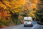 Compact white economical mini van for commercial delivery and business running on winding autumn road with yellow forest trees in Columbia Gorge area
