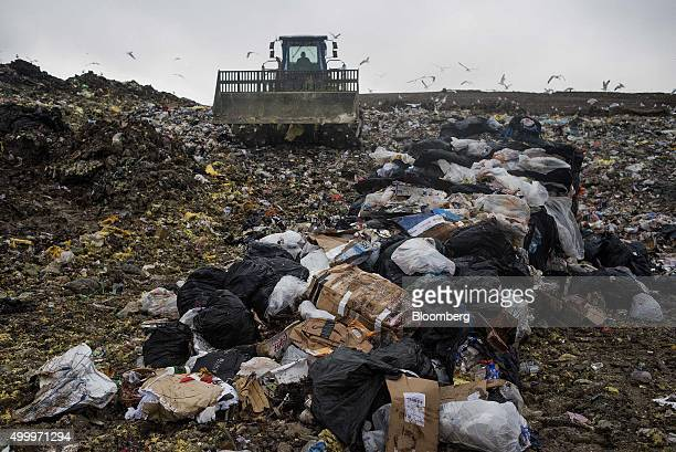 A compactor packs down trash to be covered with fresh dirt at the Defiance County Landfill in Defiance Ohio US on Wednesday Dec 2 2015 According to...