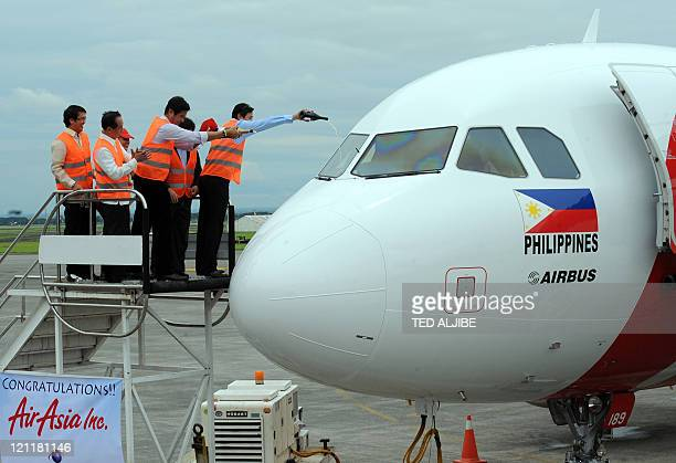 Company and airport officials pour champagne on a newly arrived AirAsia's Airbus A320 passenger aircraft at Clark airport in Angeles City Pampanga...