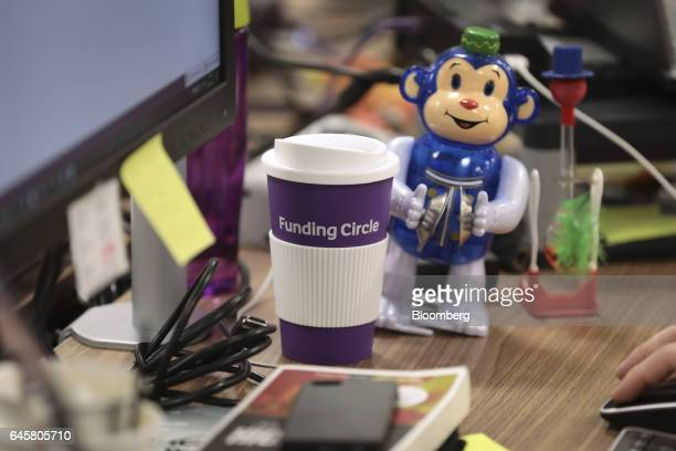 A company branded cup sits alongside a windup toy on the desk of an employee at the Funding Circle Ltd office headquarters in London UK on Wednesday...