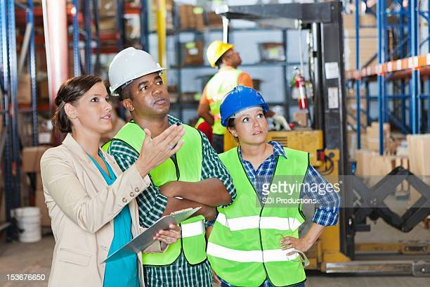 Company executive explaining order to shipping distribution warehouse workers