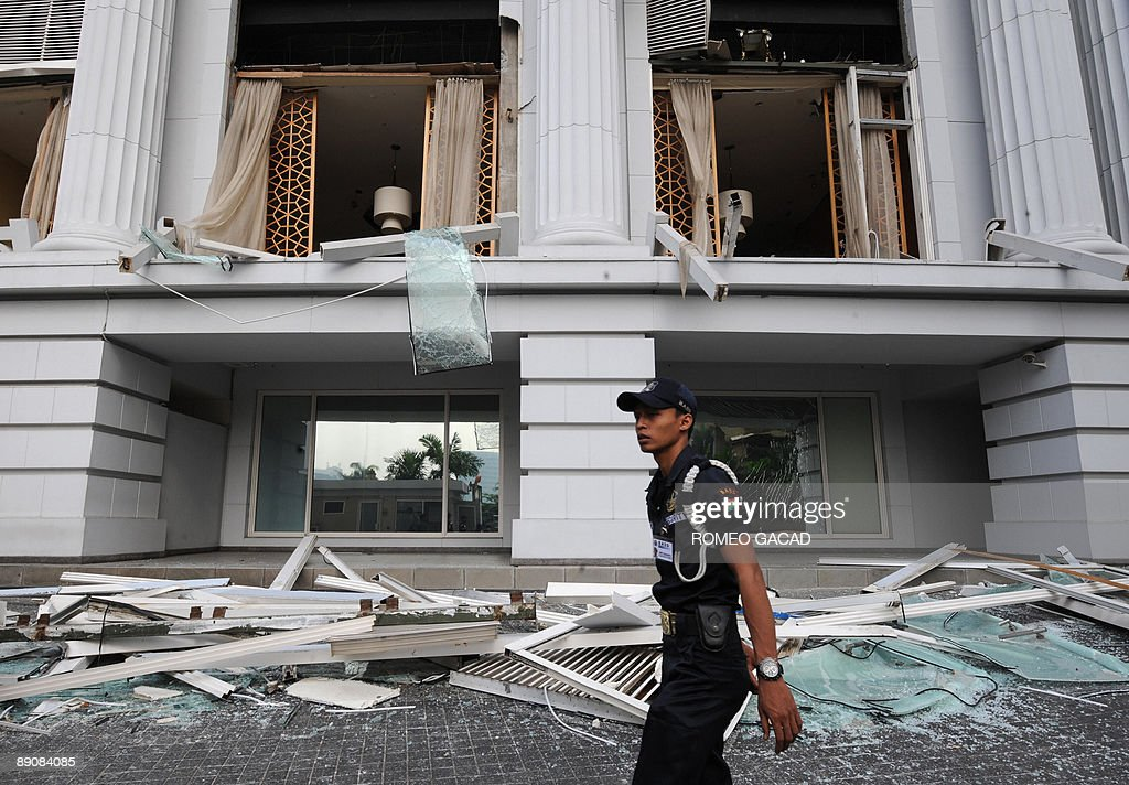 Company guard secures the damaged facade of the RitzCarlton hotel in Jakarta on July 18 2009 while investigators probe the twin bombing a day after...