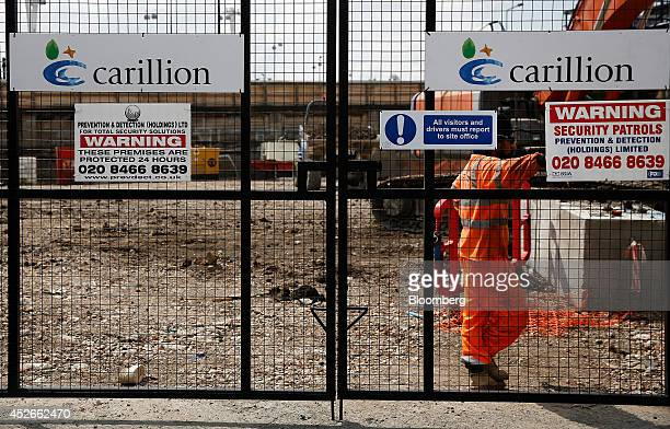 Company logos sit on the gates of a construction site for new apartment blocks built by Carillion Plc in the Canning Town district of London UK on...