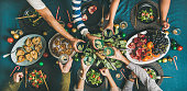 Company of friends of different ages or family gathering for Christmas or New Year party dinner at festive table. Flat-lay of human hands holding glasses with drinks, feasting and celebrating holiday