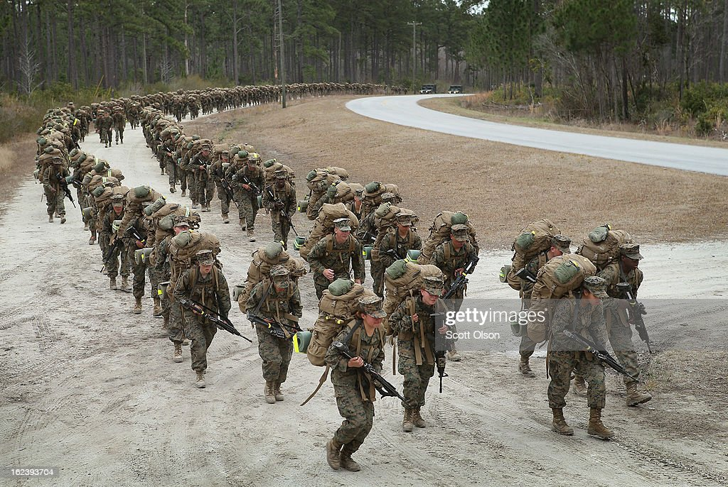 A company of Marines both male and female participate in a 10 kilometer training march carrying 55 pound packs during Marine Combat Training on...