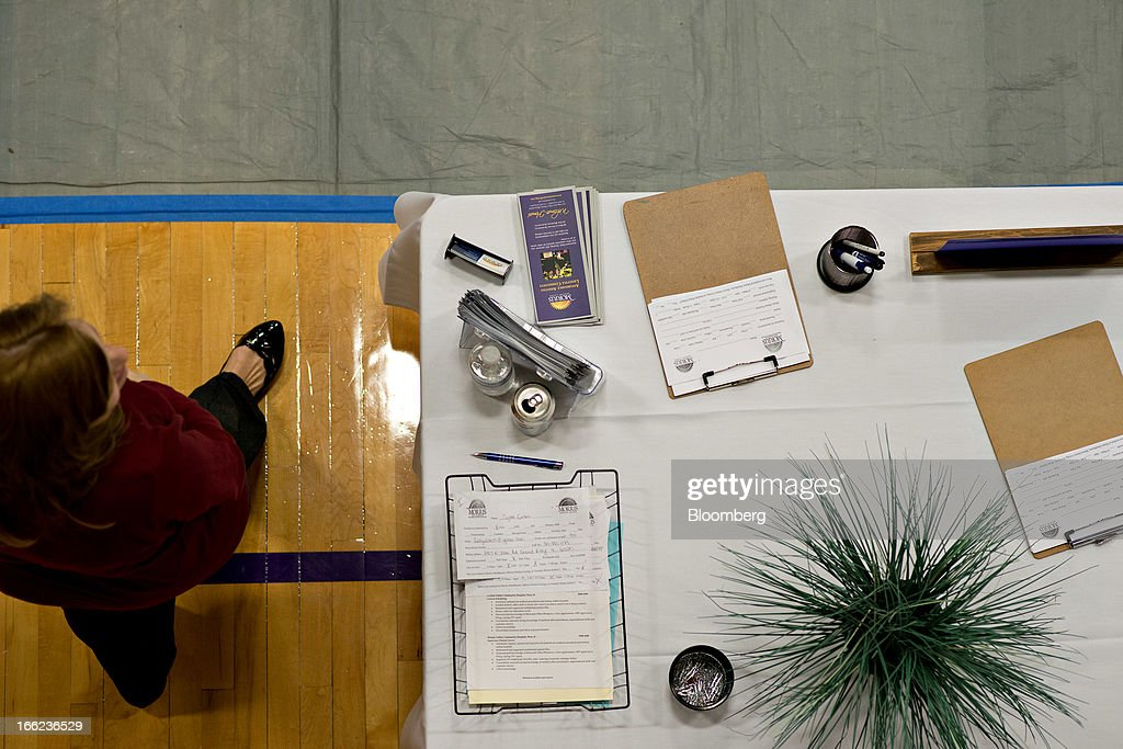 A company representative walks near an employer table during a job fair at Illinois Valley Community College (IVCC) in Oglesby, Illinois, U.S., on Wednesday, April 10, 2013. The U.S. Department of Labor is scheduled to release jobless claims figures on April 11. Photographer: Daniel Acker/Bloomberg via Getty Images