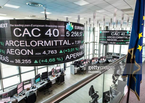 Company stock price information sits displayed on a screen as a European Union flag hangs from a pole inside the Paris stock exchange operated by...
