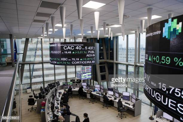 Company stock price information sits displayed on screens hanging above the Paris stock exchange operated by Euronext NV in La Defense business...
