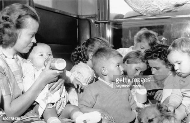 Compartiment de train rempli d'enfants accompagnés d'adultes lors de l'affluence des vacanciers dans les gares parisiennes le 29 juillet 1960 à Paris...
