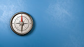 Metallic Compass with Red Magnetic Needle Pointing Toward the North Against a Plastered Blue Wall with Copyspace, 3D Illustration