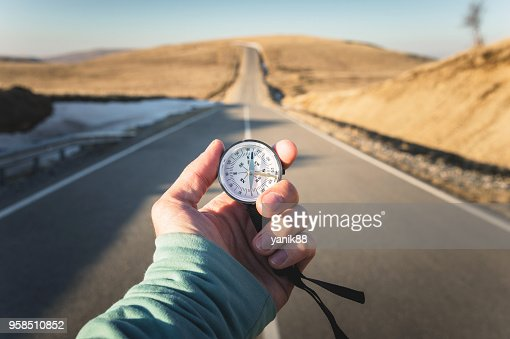 Compass in Hand mountain road background .Vintage Tone : Stock Photo