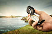 Compass in the hand traveler on the coastline near the sea background hills and mountains.