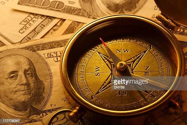 Boussole sur une pile de billets de cent dollars