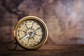 Old compass on vintage map. Retro stale. Very shallow focus.