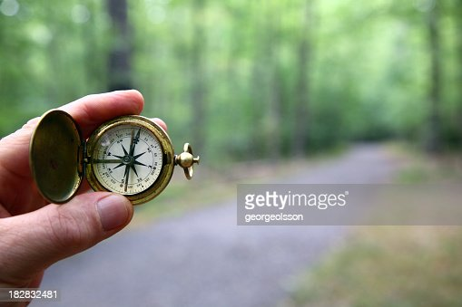 Compass With Blurred Woods Trail
