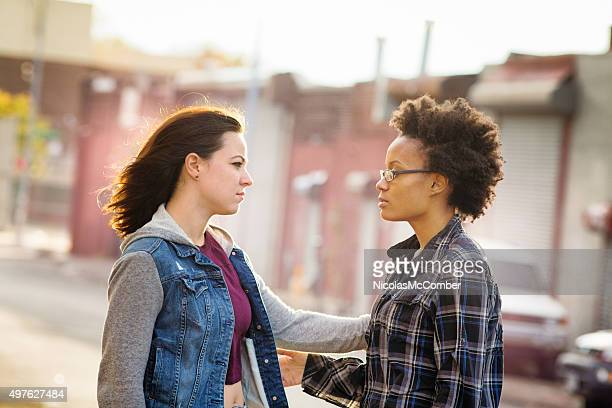 Compassionate young woman reaches out to console her friend