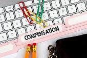 Compensation concept. Folder Register on Background of Computer Keyboard
