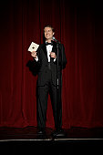 Compere holding envelope standing on stage