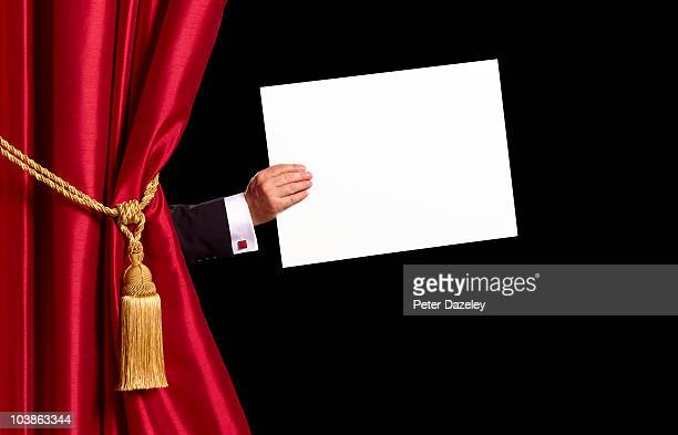 Compere holding sign with red curtains