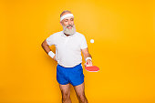 Competetive emotional cool active comic grandpa with beaming grin, with table tennis equipment. Healthcare, weight loss, bodycare lifestyle, wearing blue sexy shorts, so hot!