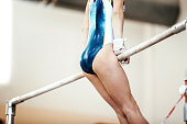 competition in gymnastics exercises on uneven bars girl gymnast