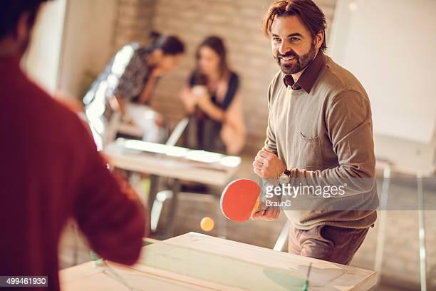 Concours de jouer au tennis de table au décontracté bureau;!