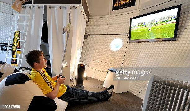 Competition winner Adam Santarossa watches the TV screen as he spends 31 days in a giant replica Jabulani World Cup ball watching all 64 games from...