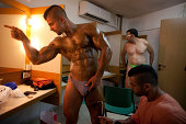 A competitior is assisted with his tanning backstage ahead of judging during the 2014 NABBA Israel Championship on August 14 2014 in Netanya Israel...