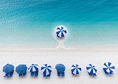 Stand out from the crowd, leadership and different concept. Umbrellas and lounge chairs next to the turquoise waters of sea.