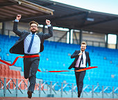 Young running businessman reaching finish at stadium