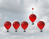 Competitive edge and business advantage concept as a group of hot air balloons racing to the top but an individualleader with a small balloon attached giving the winning competitor an extra boost to w