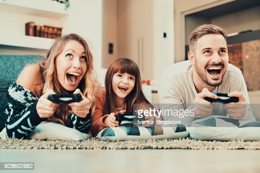 Competitive family playing video games at home : Foto de stock