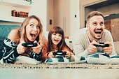 Happy family- father, mother and daughter playing a video game at home.