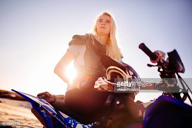Competitive female quad bike racer looking intent with sun flare