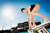 Competitive swimmer crouching on starting block
