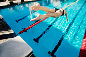 Competitive swimmer diving into swimming pool