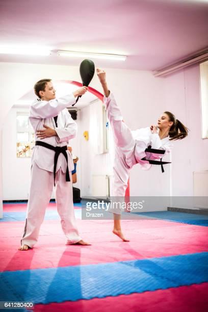 Competitive taekwondo girl on training, round kicking focus mat